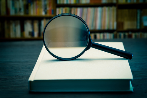 Magnifying glass on books with background of bookshelf