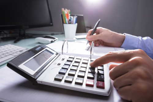 Businessperson Calculating Receipt With Calculator